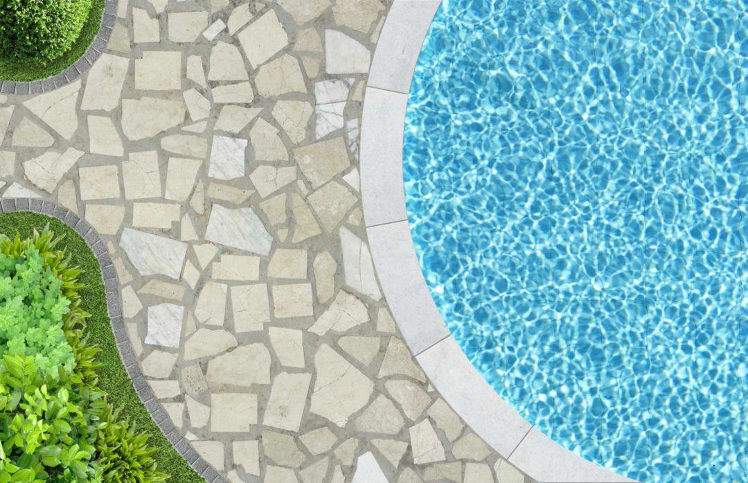 Vue aérienne d'un bord de piscine avec dallage en pierre naturelle et margelle