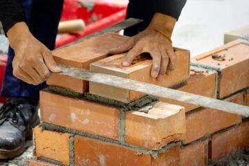 Artisan maçon réalisant un mur une clôture en brique