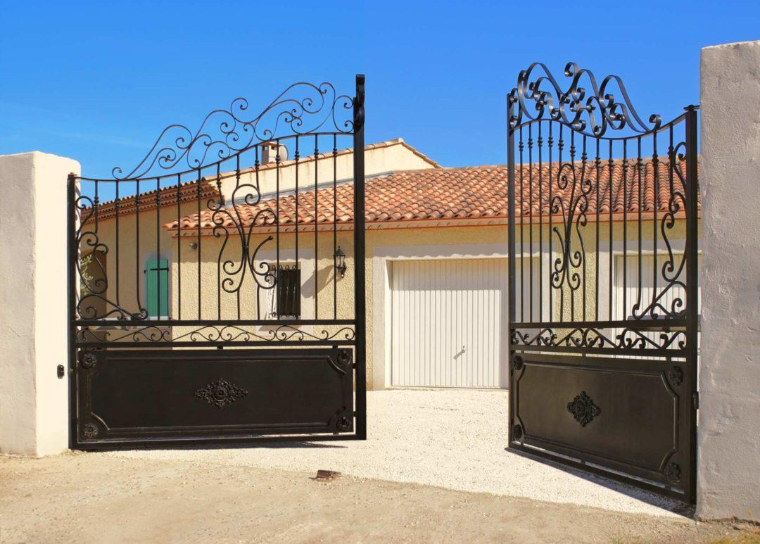Portail à battants en fer forgé ouvrant sur une maison individuelle
