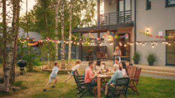 Grand jardin éclairé par les lampions pour dîner entre amis