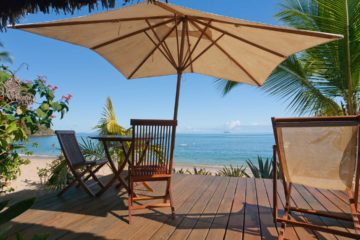 Terrasse avec transat et parasol en bord de mer