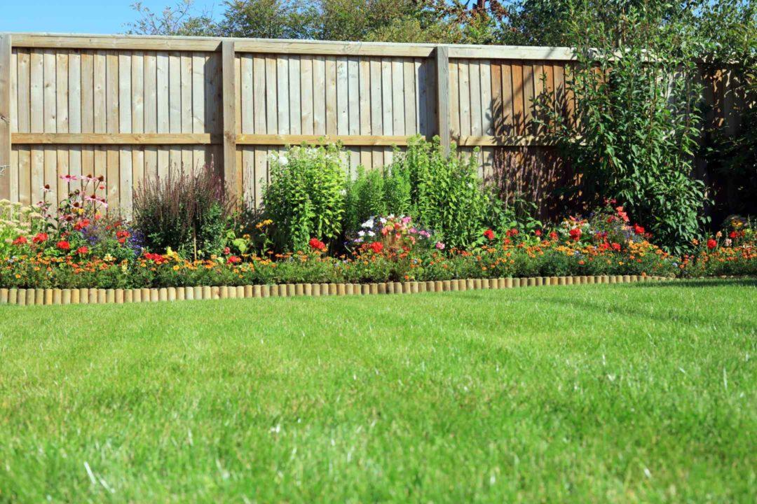 Jardin entretenu avec palissade et bordure en bois