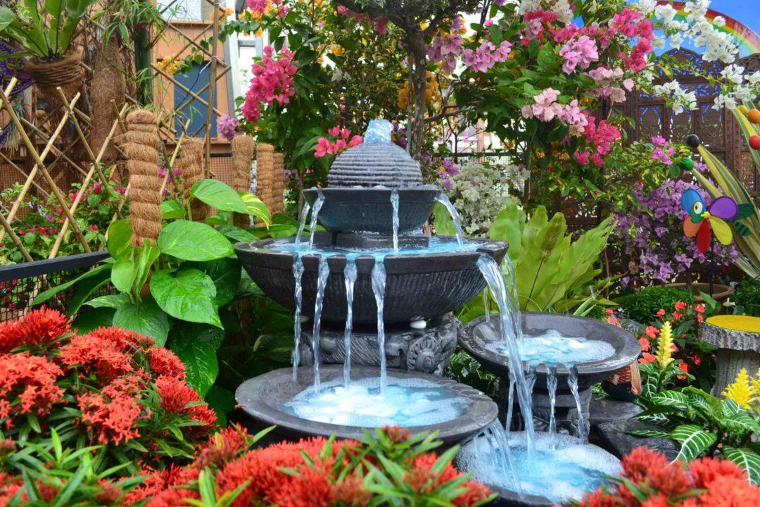Fontaine à cascade dans un jardin fleuri