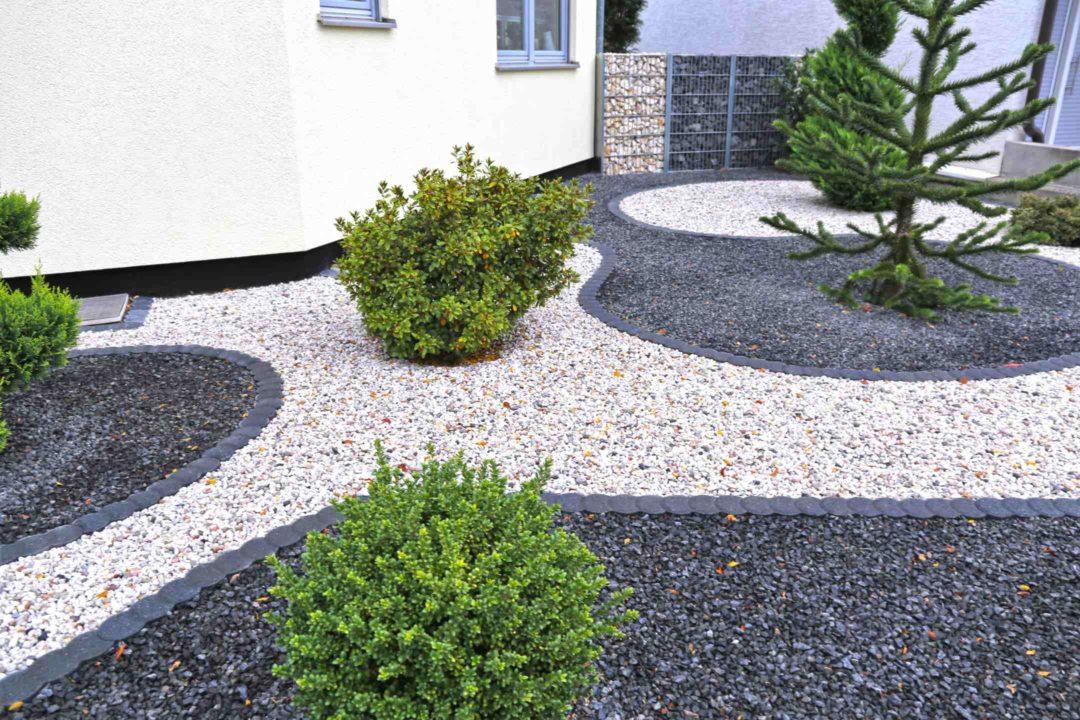 Jardin paysager aménagé avec de la pierre et des graviers blancs et noirs