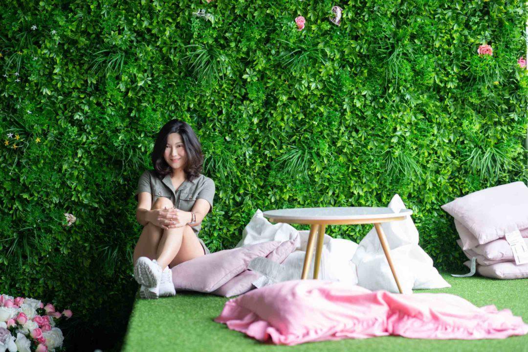 Jeune femme assise devant un mur végétal, jardin vertical