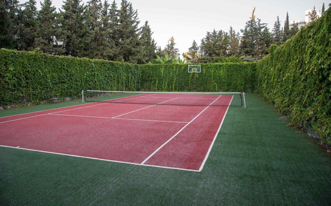 Terrain de tennis entouré d'une haute haie