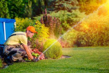 Jardinier paysagiste réglant l'arrosage automatique d'un jardin