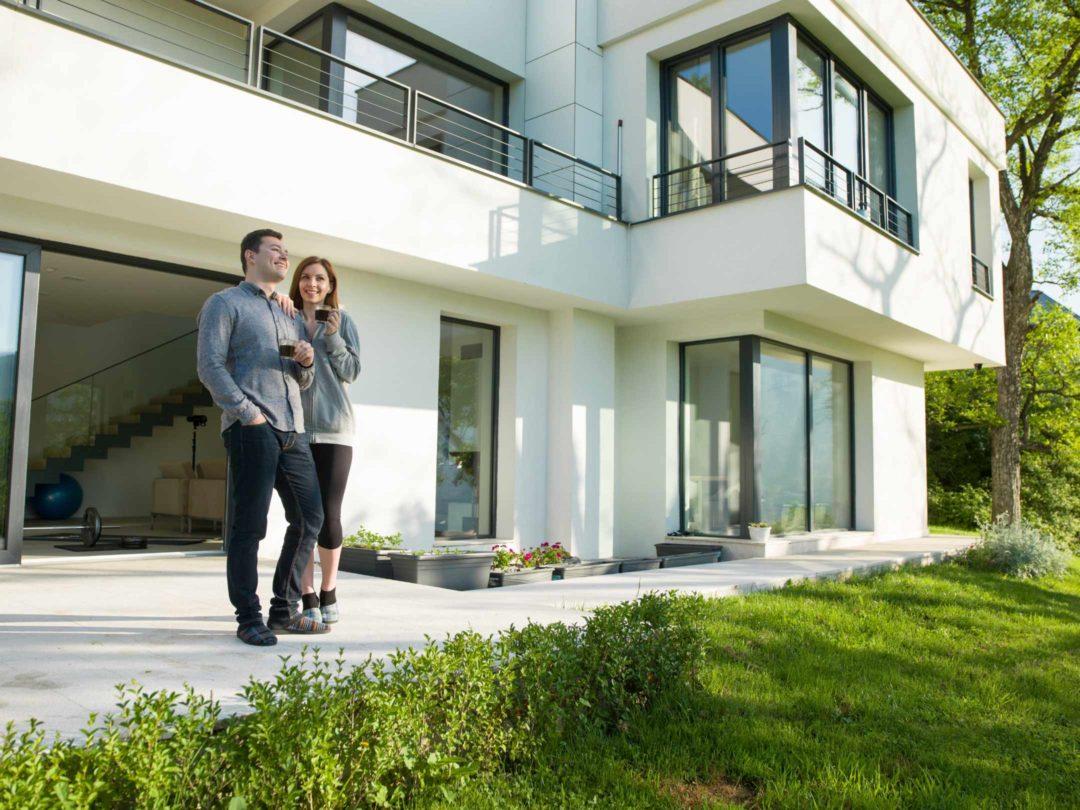 Couple prenant un café sur la terrasse d'une belle maison moderne