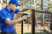 Artisan en train de poser un grillage en guise de clôture d'un jardin ou d'une maison