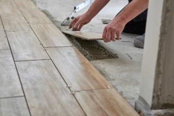 Un artisan dépose sur une terrase du carrelage avec un effet bois