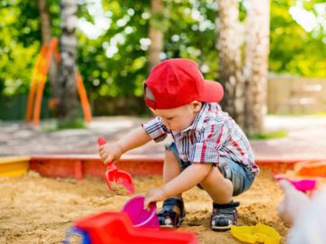 Enfant jouant dans un bac à sable aménagé dans la cour d'une maison