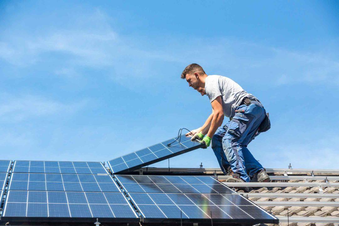 Deux ouvriers déposent des panneaux photovoltaïques sur le toit d'une maison