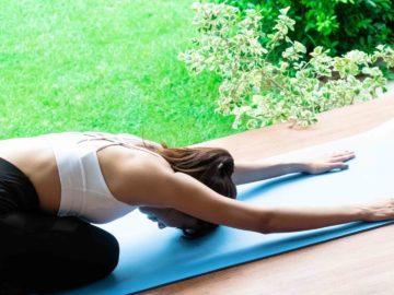 Une femme pratique du sport, du yoga, dans son jardin