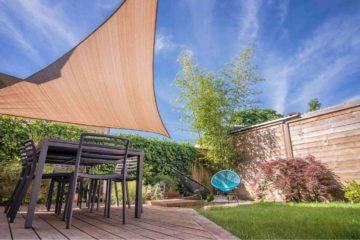 Voile d'ombrage installé au-dessus d'une terrasse aménégée