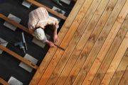 Un artisan construit une terrasse en bois dans un jardin