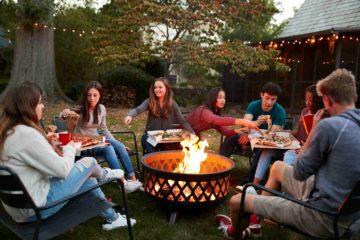 Une bande de jeunes amis réunis autour d'un brasero pour manger une pizza