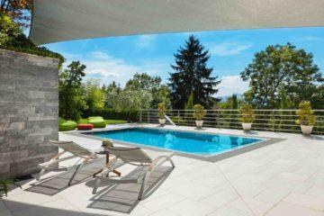 Belle piscine aménagée sur la terrasse d'une belle maison avec grand jardin