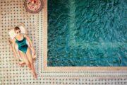 Une femme prend un bain de soleil au bord d'une belle piscine