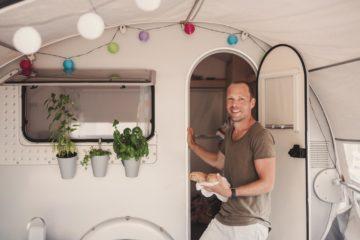 Un homme à l'entrée d'une caravane stationnée dans un jardin