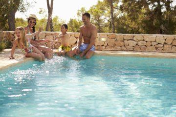 Un couple et ses deux enfants au bord d'une belle piscine entourée d'un mur de pierre