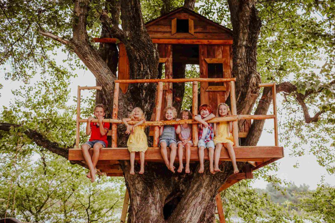 Un groupe d'enfants dans une cabane en bois construite dans un arbre