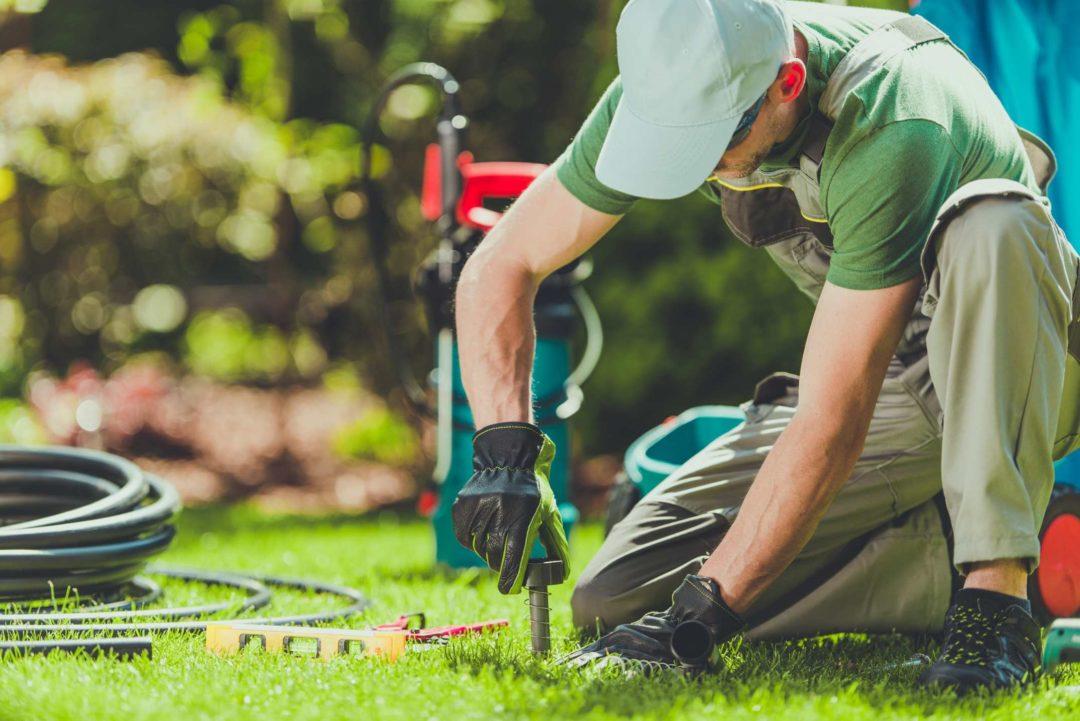 Un artisan installe un arrosage automatique dans un jardin