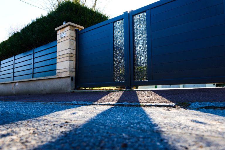 Le portail à motifs personnalisés et sa longue clôture