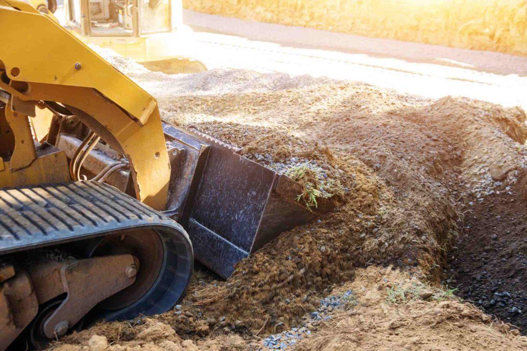 Un engin de chantier effectue des travaux de terrassement dans un jardin particulier