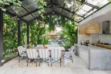 Une belle cuisine d'été installée dans un jardin paysager avec piscine en fond