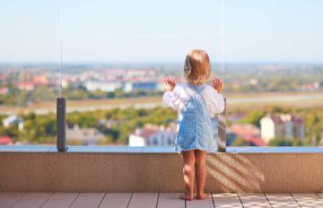 Une jeune enfant regarde le paysage sur un terrasse protégée par un garde corps