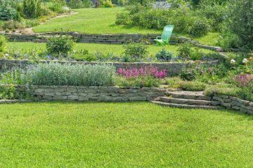 Un beau jardin paysager en terrasse avec pierre naturelle et pelouse