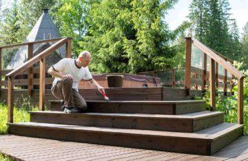Un homme entretien un escalier en bois menant à un jacuzzi dans un jardin paysager