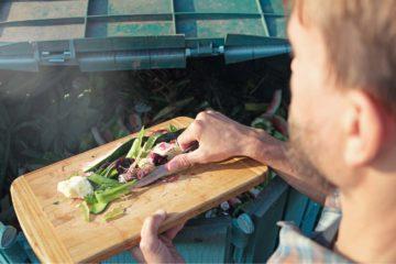 Un homme dépose des déchets organiques et alimentaires dans un composteur