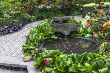 Une fontaine d'inspiration asiatique au sein d'un espace détente dans un jardin paysager