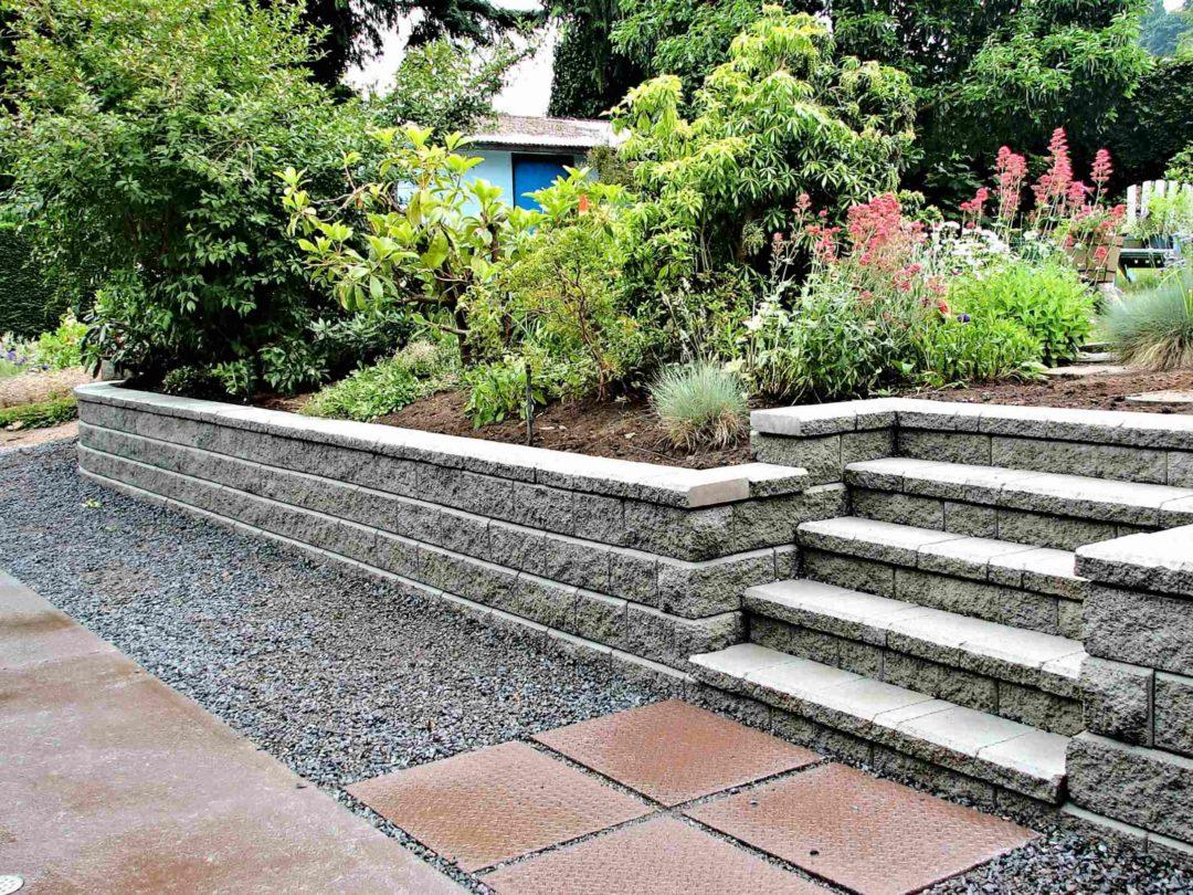 Un jardin paysager avec une retenue de terre habillée de pierres