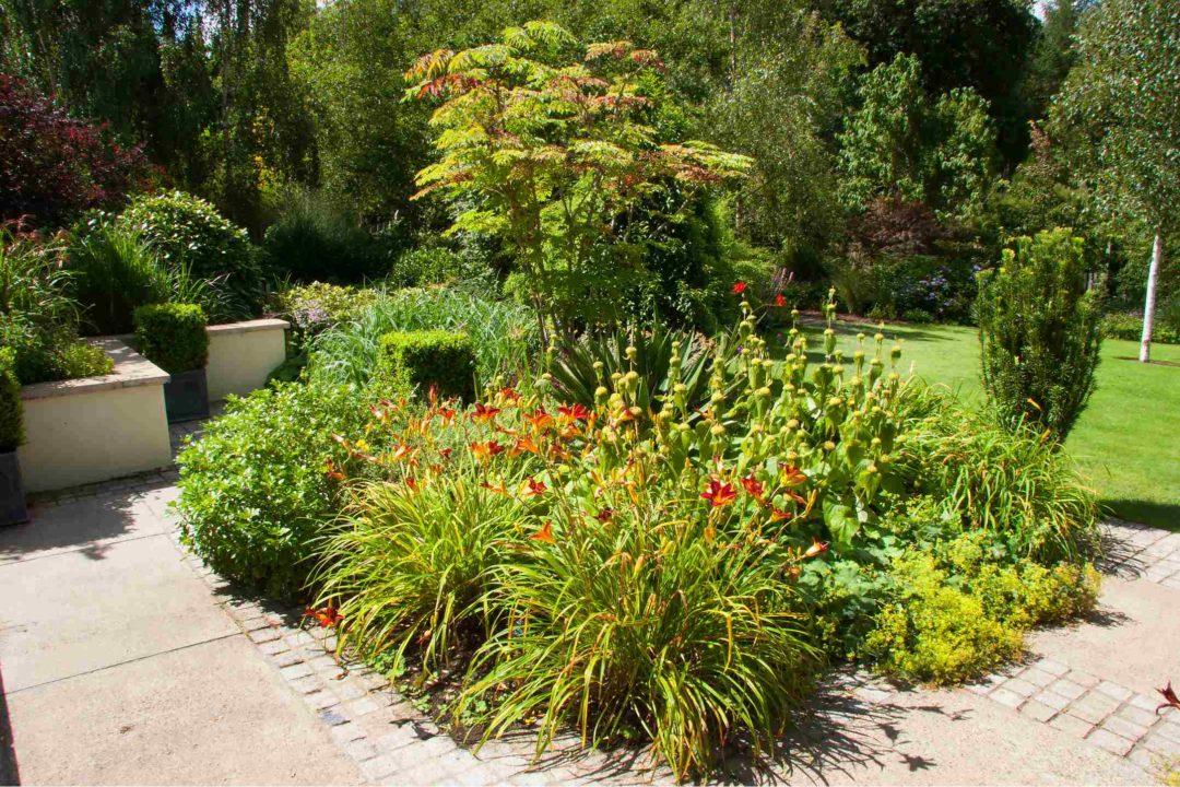 Un massif de plantes et de fleurs à l'entrée d'une propriété