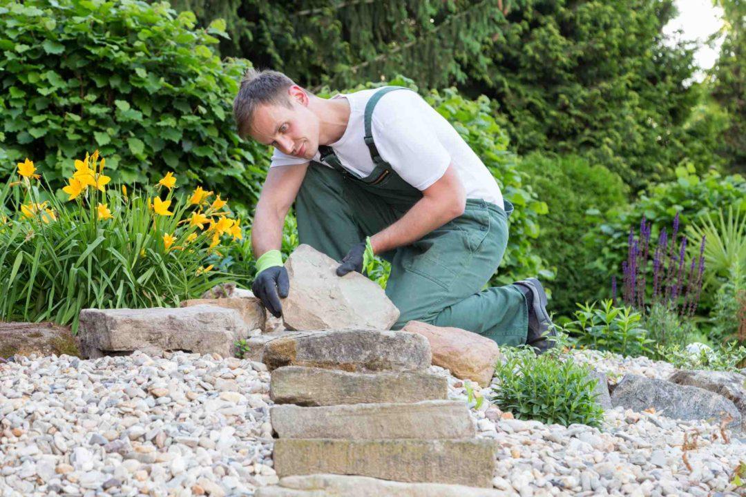 un jardinier paysagiste réalise un escalier avec des pierres naturelles dans un jardin privé