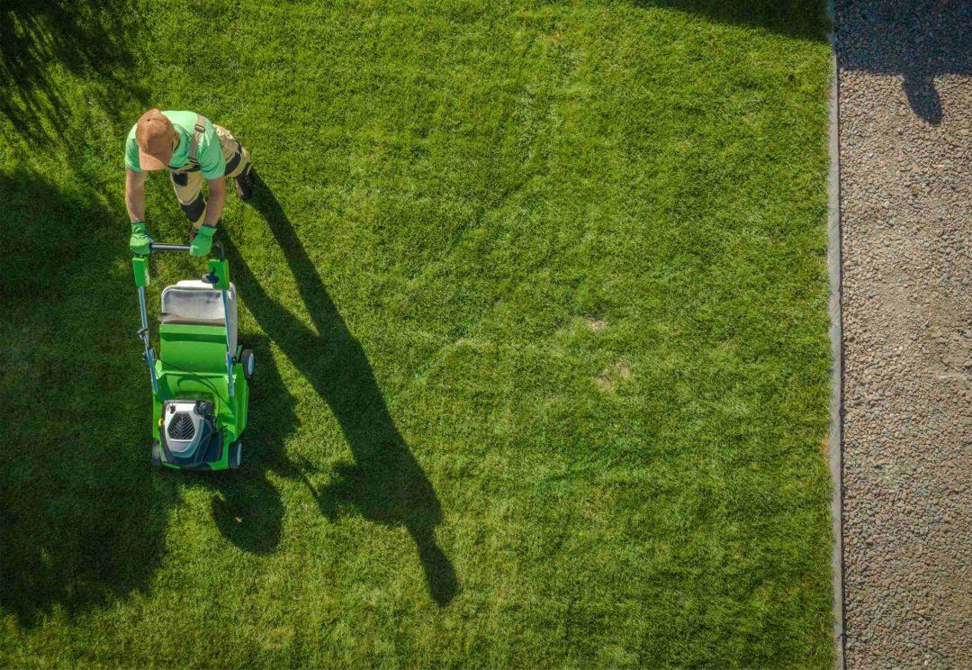 Un jardien passe la tondeuse sur une pelouse dans un jardin particulier