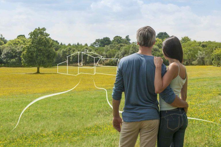 Un couple et la projection de leur futur maison sur un terrain nu