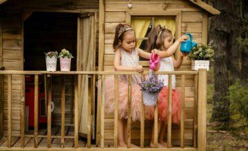 Deux petites filles jourent devant une cabane en bois dans un jardin