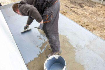 Un artisan/ouvrier fait des travaux d'étanchéité d'une terrasse