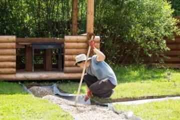 Un artisan paysagiste étale du gravier sur un film géotxtile dans un jardin