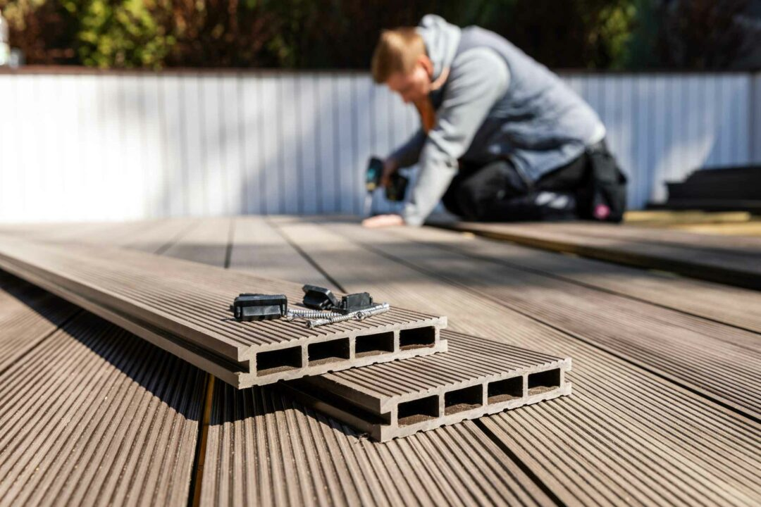 Un artisan pose du bois composite sur une terrasse