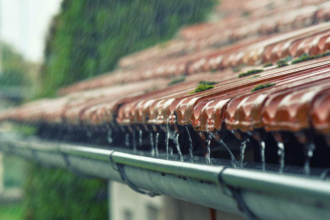 Le toit d'une maison et sa gouttière lors d'un jour de pluie