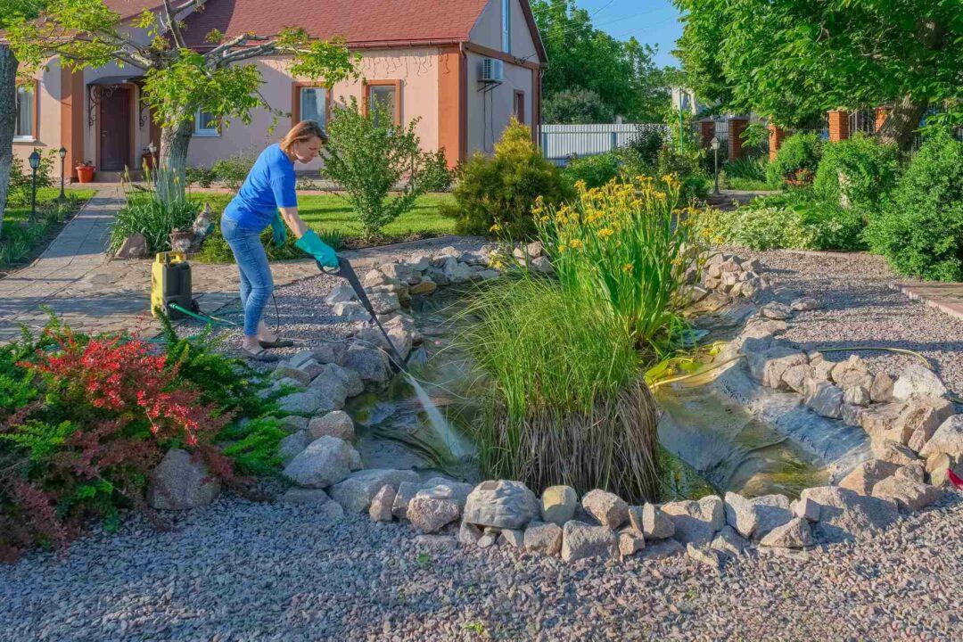Une femme nettoie un bassin artificiel (mare) dans son jardin