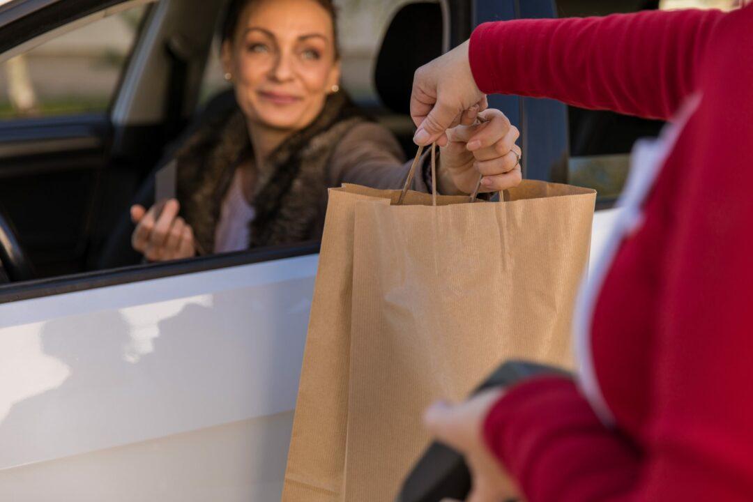Une femme réceptionne dans un drive des articles commandés en ligne