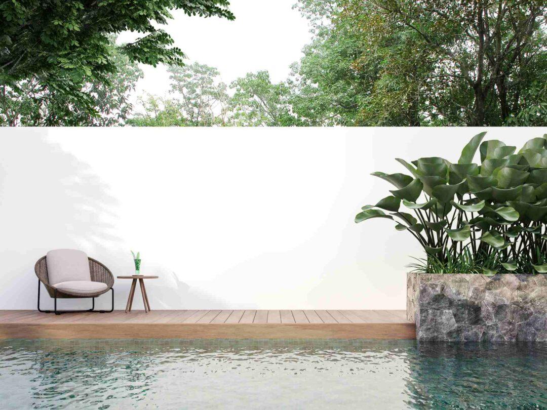 Un mur mitoyen peint en blac derrière une belle piscine