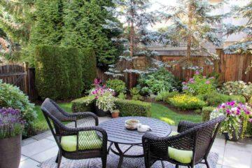 Une idée d'aménagement d'un agle de jardin avec palissade, plantes, arbres et et arbustes