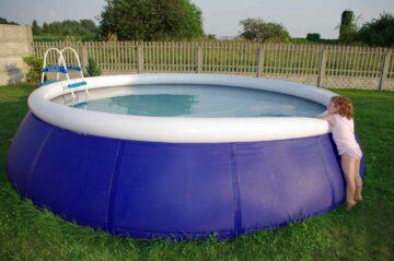 Un enfant devant une piscine autoportante installée dans un jardin