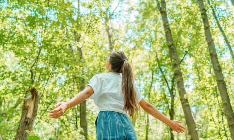 Une femme profite du bon air dans une forêt